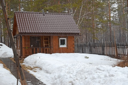 sleet: Bathhouse in the inner yard of country house. Spring sleet in the village. Siberia, Russia