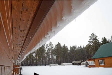 sleet: Snow visor with icicles  slipping from canopy roof. Spring sleet in the village. Siberia, Russia