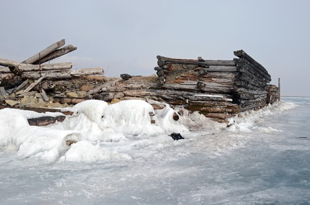 Old ruined wooden pier in ice in the village of Big Goloustnoye. Russia, Baikal Lake