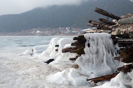 Iced old ruined wooden pier with Large Goloustnoye Village on background. Russia, Baikal Lake Stock Photo