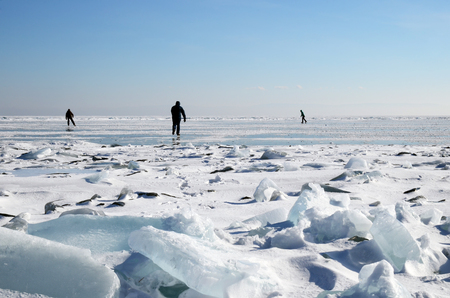 The skaters on Baikal ice between cracks and hummocks. Winter activities