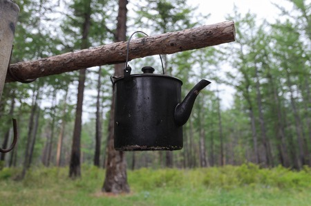 Kettle on stick over bonfire in tourist camp on Baikal Lake coast Stock Photo