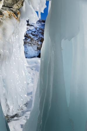 Ice splashes of waves on shores of Baikal, Ice blocks and icicles on coast rocks. Stockfoto