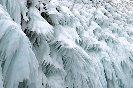 Ice splashes on frozen rocks and stones, formed during freezing of lake