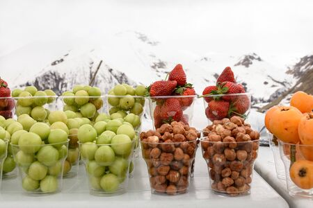 Pieces of fresh fruit in glasses on background of Caucasus Mountains among the snows, Georgia