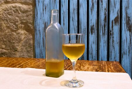 Transparent bottle and glass of white on table. Wooden blue background in rustic style