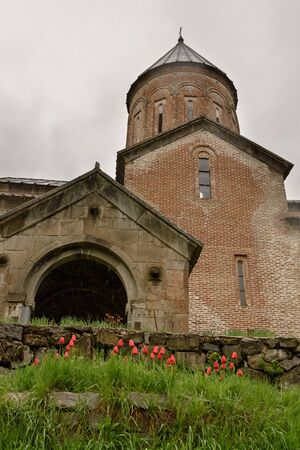 Church of Assumption of Blessed Virgin Mary in Timotesubani Monastery with tulips in front of entrance in rainy day