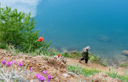 Spring flowers and figure of fisherman on background of Tbilisi reservoir water, Georgia