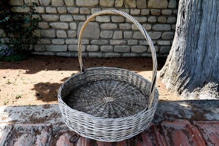 Large old round wicker basket with curved handle, courtyard of Georgian monastery