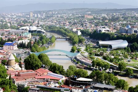 Kura river, modern futuristic bridge, art objects and old streets in central part of Tbilisi, Georgia. Top view 写真素材 - 135103585
