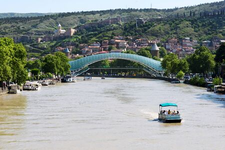 Kura river and modern futuristic glass bridge, center of Tbilisi, Georgia 写真素材 - 134617915