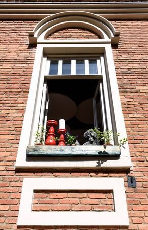 Open window in brick house, red candlesticks and potted flowers on windowsill