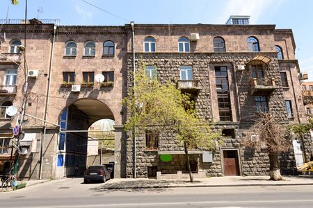 Residential building in center of Yerevan, built of traditional pink tuff - volcanic rock, Armenia 写真素材 - 137874675