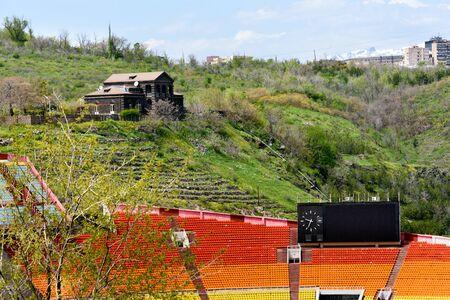 The stands of Hrazdan Stadium and house on hill. Yerevan, Armenia