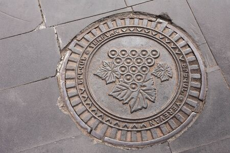 Erevan, Armenia-April, 28 2019: Sewer Hatch with bunch of grapes Image on Erevan street. Armenia