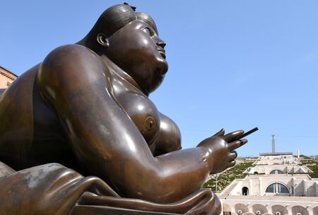 Yerevan, Armenia-April, 29 2019: Lady with cigarette in alley at the foot of Cascade in center of Yerevan, Colombian sculptor Fernando Botero
