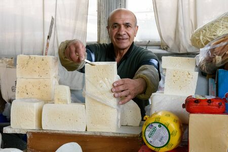 Yerevan, Armenia-April, 29 2019: Seller at grocery market in Yerevan cuts cheese to give try, Armenia 報道画像