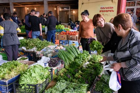 Yerevan, Armenia-April, 29 2019: Buyers and sellers near boxes of fresh herbs and vegetables at the grocery market in Yerevan, Armenia