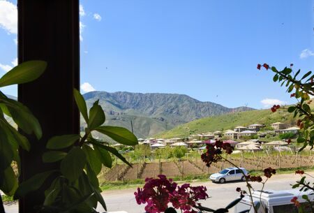 Winery mountain village of Areni in Armenia. View through window with indoor flowers out of focus 写真素材