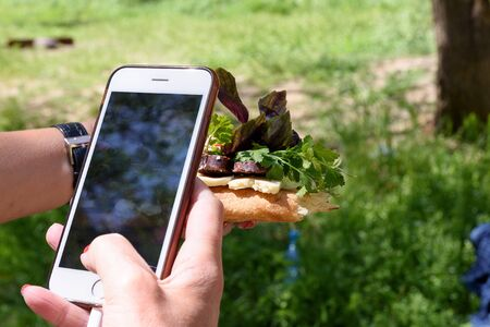 Mobile phone in female hand - makes photo of sandwich of pita bread, sujuk, basil and parsley in the hand. Outdoor picnic