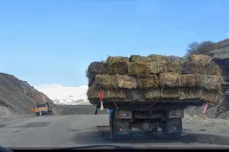 View through car windshield of road and truck in front loaded with hay briquettes. Armenia