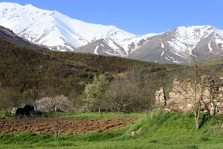 Arable land and the ruins of a stone wall on the background of snow-capped mountains. Armenia, Tatev, Syunik region