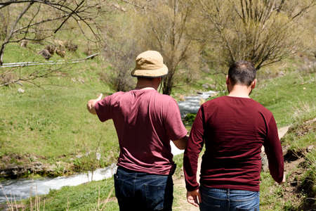 Two men walk along small river in spring