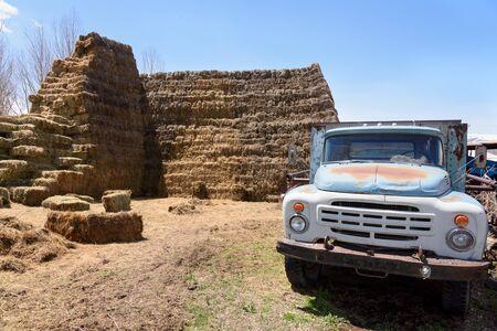 Old truck in yard with hay blocks. Armenian village