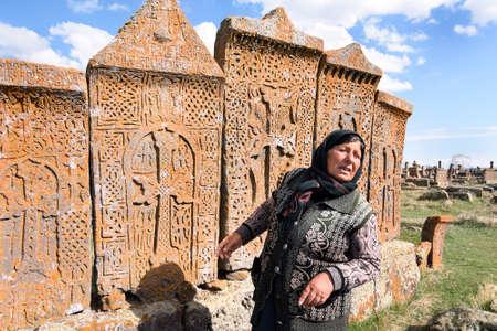 Noratus, Armenia-May, 01 2019: unique cemetery of khachkars, Old Armenian woman talk about khachkars. Armenia