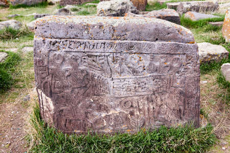 Noratus, Armenia-May, 01 2019: headstone with scene from life of Armenian family. Unique lagest cemetery of khachkars, Armenia