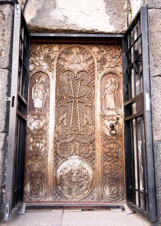 Sevan peninsula. Armenia-May, 01 2019: Carved wooden door with biblical plot. Sourp Arakelots, Sevanavank monastery, Armenia