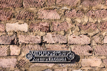 Dilijan, Armenia-May, 02 2019: sign with street name and house number on brick wall, Armenia