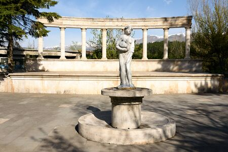 Scene of Old Amphitheater and sculpture of woman with jug on mountains backfround. Dilijan, Armenia