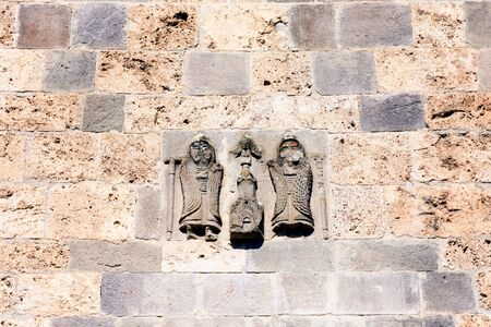 Patron bas-relief on facade Surb Astvatsatsin in Ancient Armenian monastery Haghartsin. Depicts two men monastic attire, pointing model church placed between them and image eagle with half-open wings 写真素材