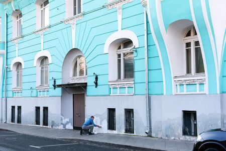 Blue house of old architecture in center of Moscow. Worker plastering facade 写真素材