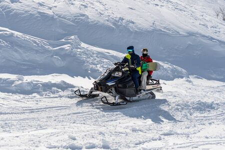 snowmobile in spring afternoon on a mountainside in bright sunshine 版權商用圖片