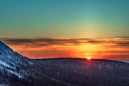 Sunset in the winter forest in the snowy expanses Standard-Bild
