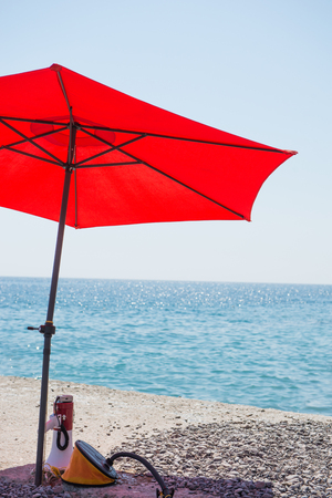 rescuer: Resting place of sea rescuer. Under the umbrella, creating a shadow are lifeguard accessories. Speaker and the pump are under the umbrella