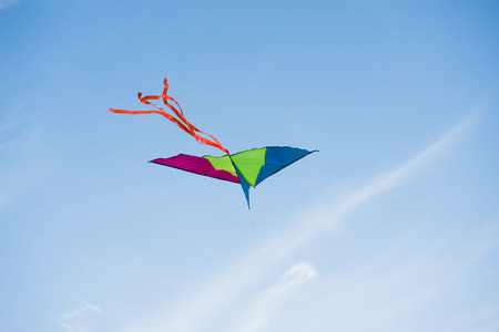 tinkering: A multicolored kite flying against a blue sky. Stock Photo