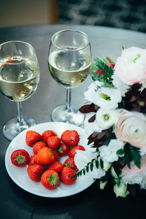 romantic evening with wine: Prenuptial romantic morning. On the table there are glasses with champagne and strawberries.