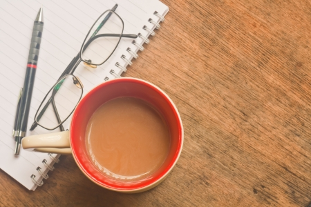 The cup of coffee and notebook on old brown wood Stock Photo - 11086432