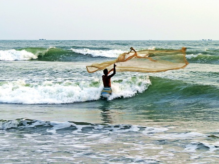 fisher man throws his net for the first catch of the day, Cox Bazar, Bangladesh