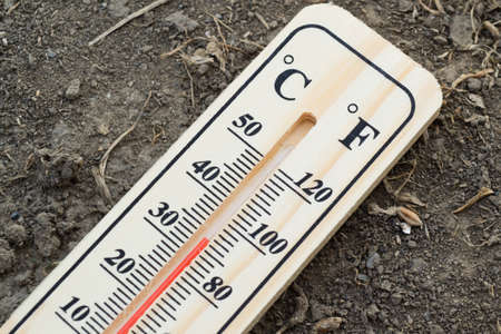 Wooden thermometer with mercury, indicating high temperature at summer, on the ground. Celsius and Fahrenheit scale.