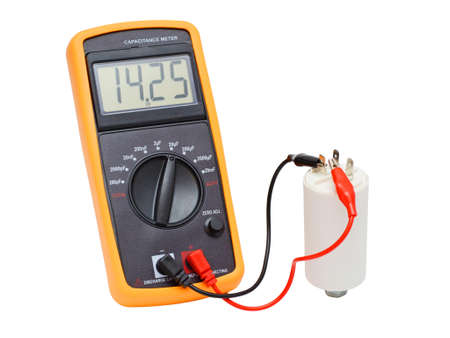 Digital multimeter isolated on white. Capacitance meter checking a white electric motor capacitor.