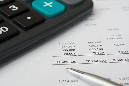 financial accounting report with pen and calculator Stock Photo