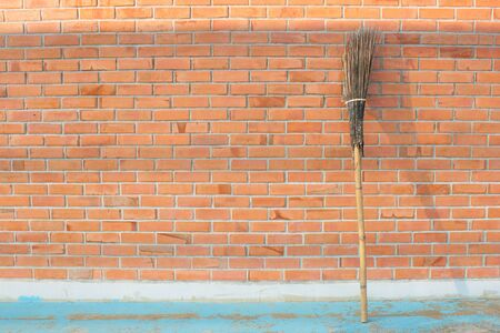 wooden broomstick  on red brick wall