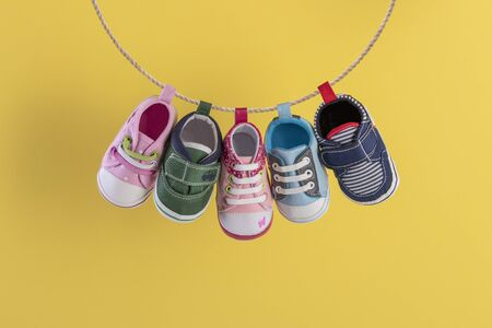 Baby shoes hanging on the clothesline on yellow background Stok Fotoğraf