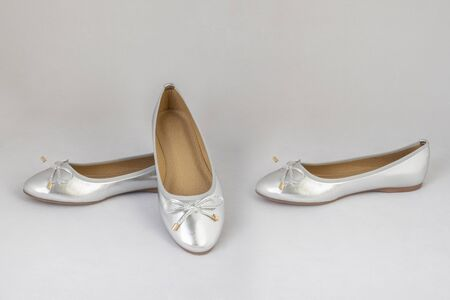 Ladies silver reflective flat shoes on white background