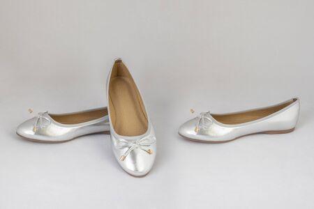 Scarpe basse da donna riflettenti argento su sfondo bianco