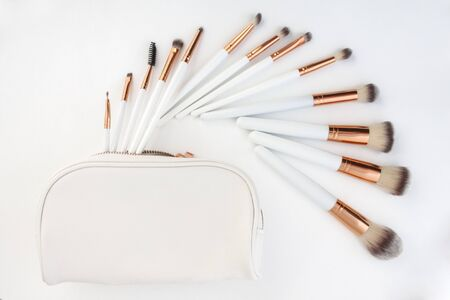 set of make-up brushes, shot on white background grouped together and counterbalanced by a larger powder brush